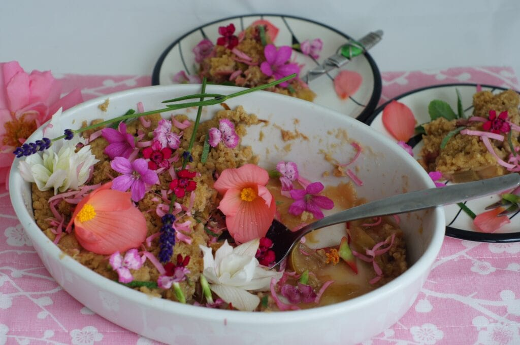 De rabarbercrumble versierd met lavendel, begonia (wit en roze), ooievaarsbekje, duizendschoon (lichroze), grasanjertjes (felroze) en in smalle reepjes gesneden rozenblaadjes.